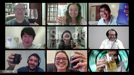 Great example of how technology can facilitate social distance during crises that require staying at home.   Case of during pandemic isolation by COVID-19. Friends drinking and toasting in a happy meeting by computer.