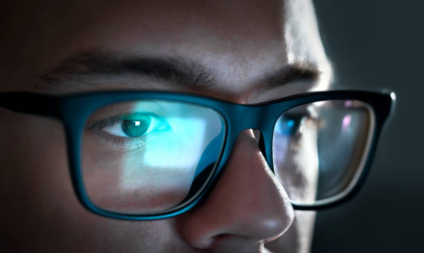 computer screen light reflect from glasses. close up of eyes. business man, coder or programmer working late at night with laptop. thoughtful focused guy in dark. - отражение стоковые фото и изображения
