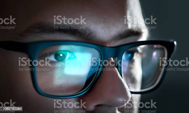 Photo of Computer screen light reflect from glasses. Close up of eyes. Business man, coder or programmer working late at night with laptop. Thoughtful focused guy in dark.