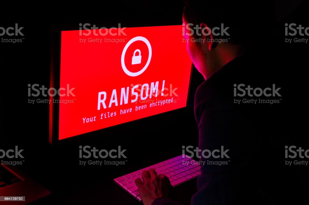 Computer screen with ransomware attack file encrypted alert in red and a man in suit keying on keyboard in a dark room, ideal for online security and digital crime stock photo