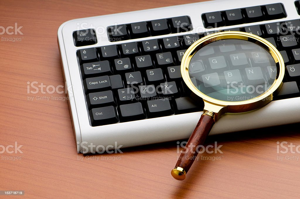 Computer security concept with keyboard and magnifying glass royalty-free stock photo