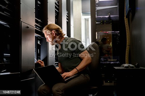 A male network server technician repairs and programmes a computer server in a university.