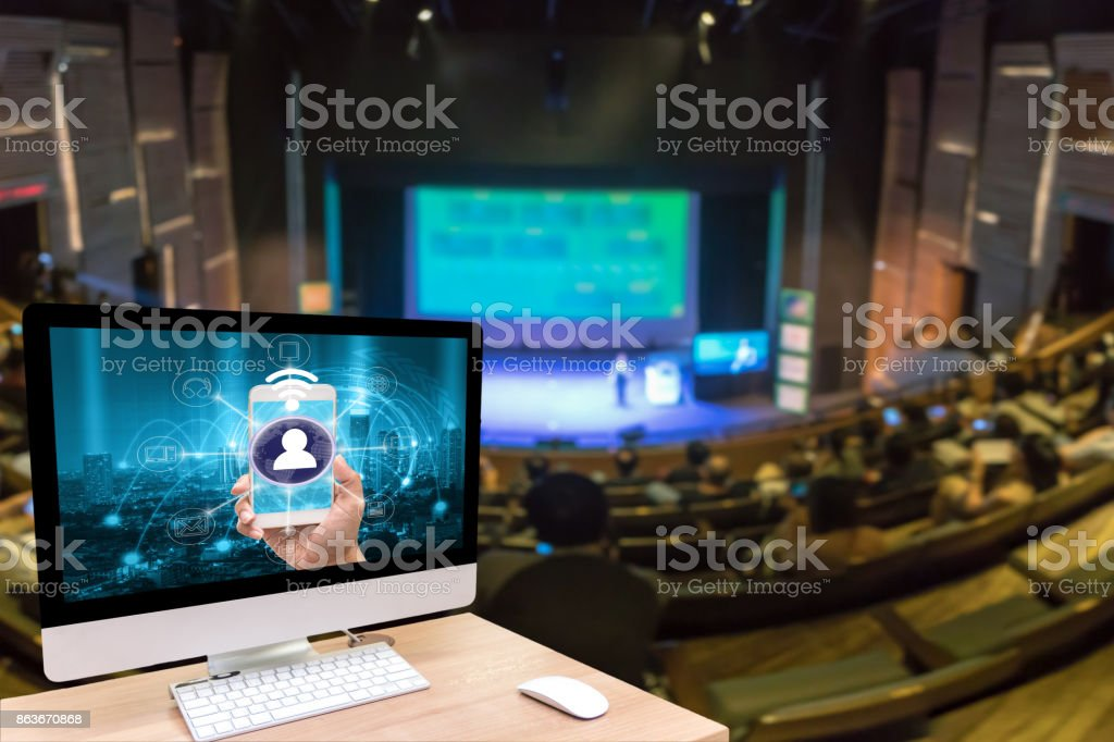 Computer set showing the mobile payments and online shopping with moni channel screen over the Abstract blurred photo of seminar room with attende background, business and education concept stock photo