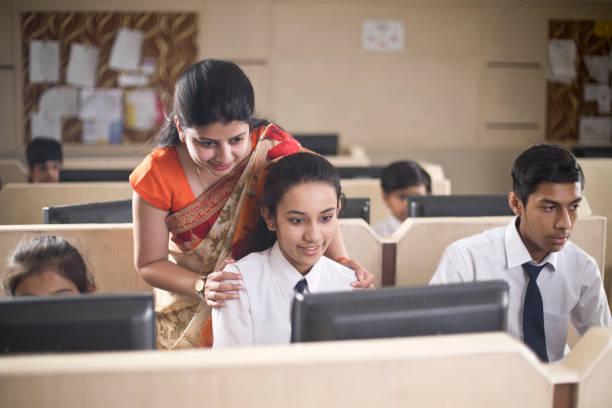 Computerlehrer unterstützt einen Schüler – Foto