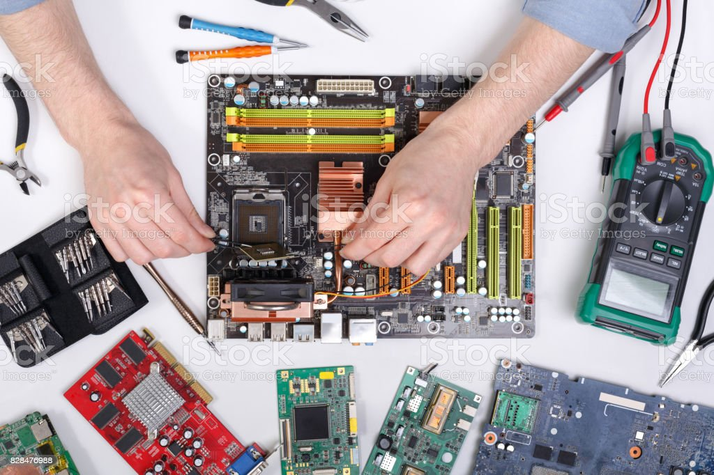 Computer upgrade. Technician plug in microprocessor to motherboa Computer upgrade of motherboard in service center top view. Technician plug in CPU microprocessor. Technology maintenance, electronics repair shop concept Backgrounds Stock Photo