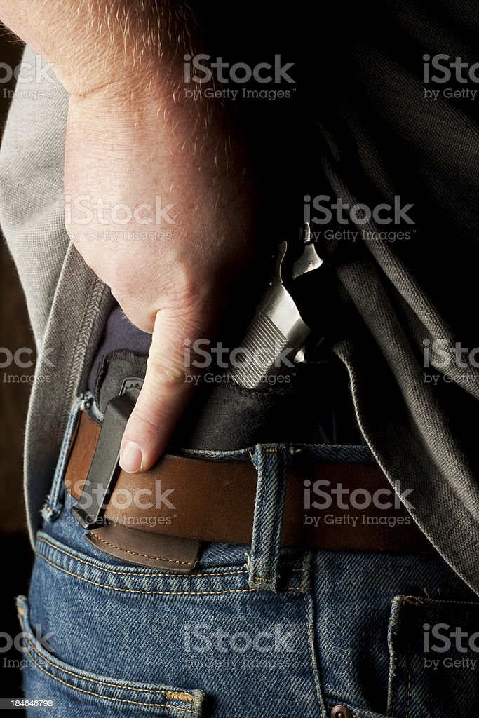 Concealed Carry Firearm Drawn From an Inside-the-Waistband Holster stock photo