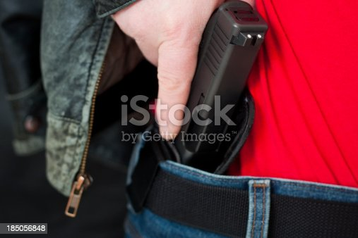 A caucasian man drawing his modern polymer (Glock) .45 caliber pistol from an IWB (inside the waistband) holster under his leather jacket.  Showing proper trigger control by keeping his finger off the trigger as he draws.All images in this series...