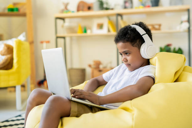 Concentrated adorable schoolkid in headphones looking at laptop display stock photo