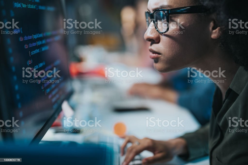 Concentrated African American programmer reading computer codes on desktop PC. stock photo