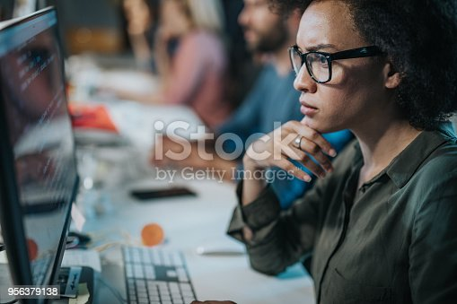 African American female programmer brainstorming while working on computer codes in the office.