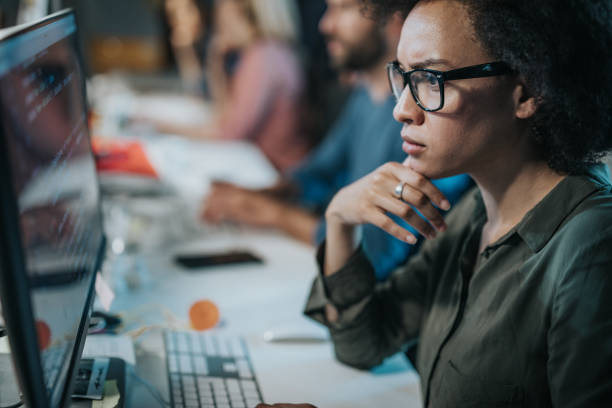 Concentrated African American woman brainstorming while coding data on desktop PC. stock photo