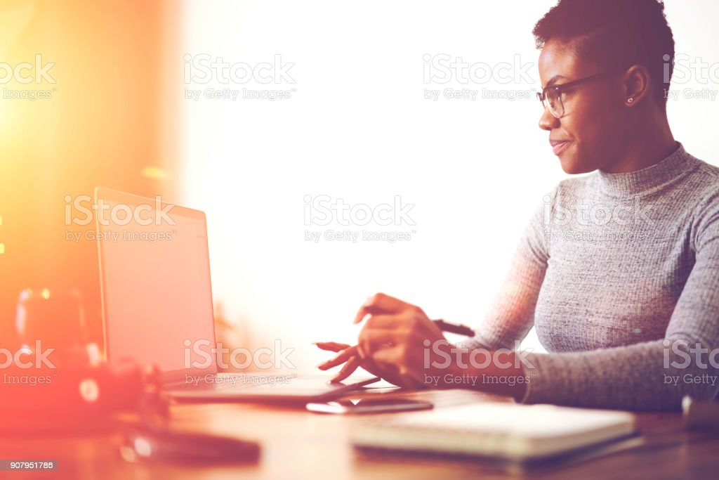 Concentrated afro american copywriter updating software on laptop computer with mock up screen in office,professional web designer analyzing information while working with application for planning stock photo