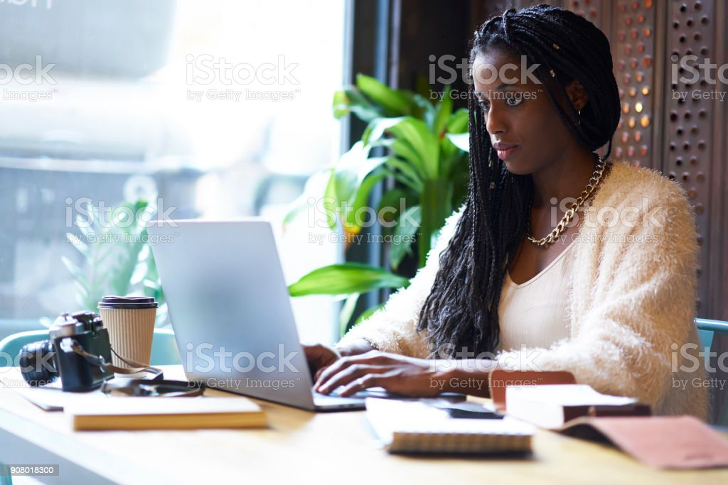 Concentrated afro american female international student of tourism making traveling planning practicing in agency using information from websites working in coffee shop uaing modern laptop computer stock photo
