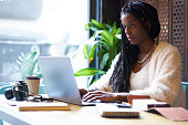 Concentrated afro american  freelancer with cornrows typing on keyboard of modern laptop text information in internet websites for searching ideas and creating startup project of business company