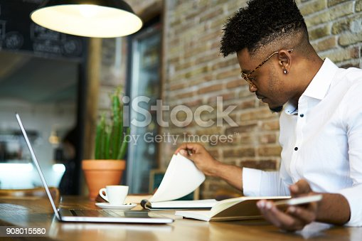 istock Concentrated afro american male finance advisor checking documentation and accounting reports of company income to create successful strategy for increasing sales working in cafe using gadgets 908015580