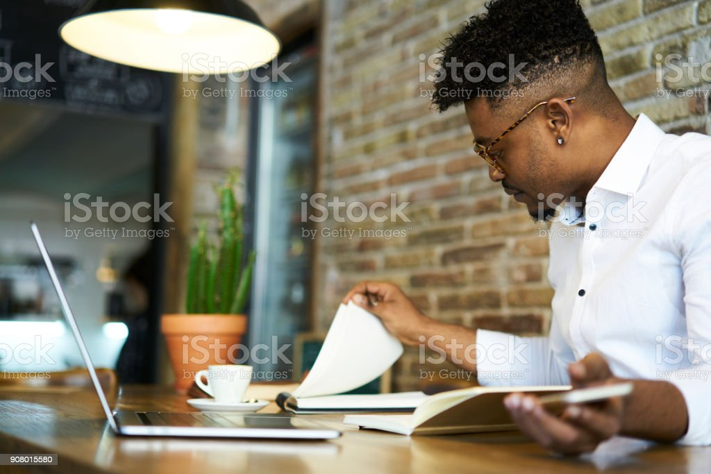 Concentrated afro american male finance advisor checking documentation and accounting reports of company income to create successful strategy for increasing sales working in cafe using gadgets stock photo