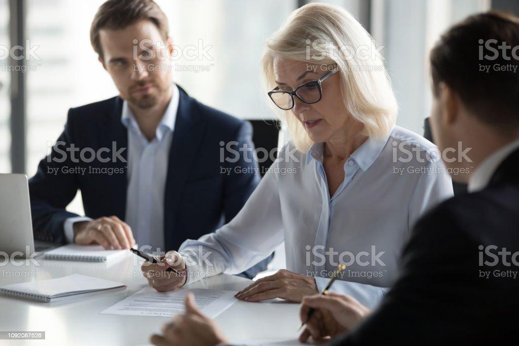Konzentriert Alter Geschäftsfrau Vertrag vor der Unterzeichnung prüfen - Lizenzfrei Abmachung Stock-Foto