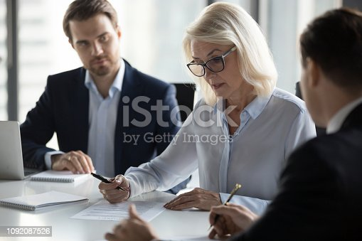 istock Concentrated aged businesswoman checking agreement before signing 1092087526