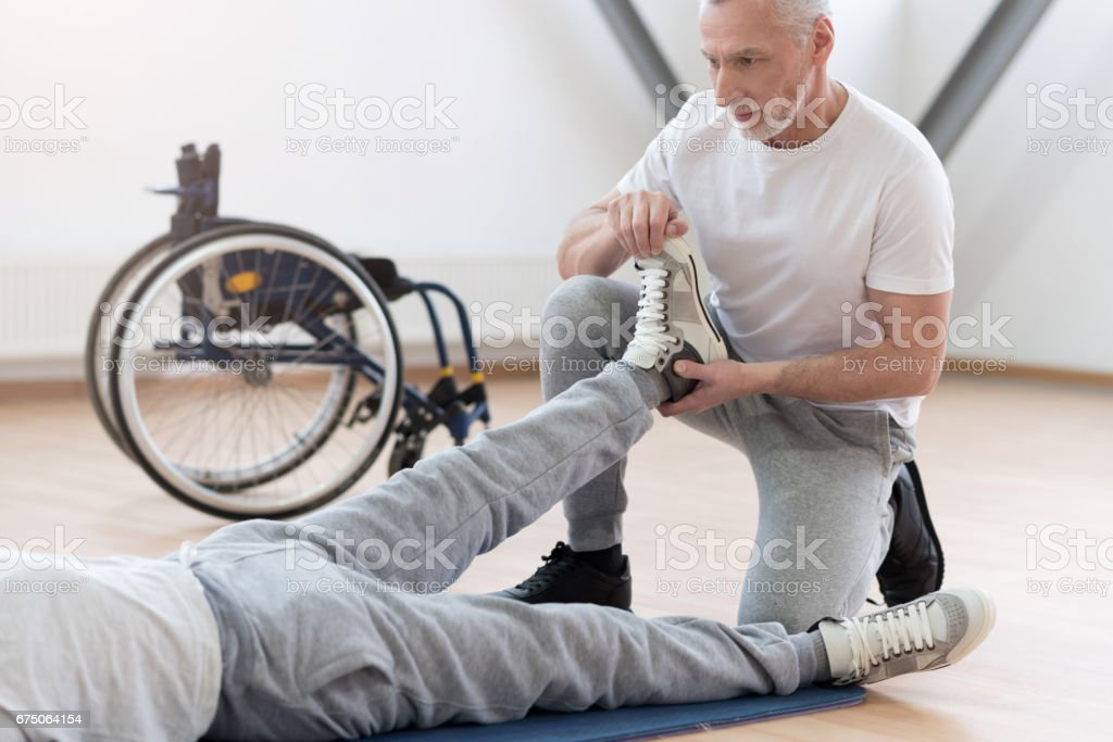 Concentrated aged orthopedist helping the disabled patient in the