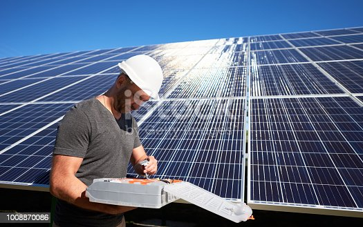istock Concentrated architect keeping equipment standing near solar panels. 1008870086