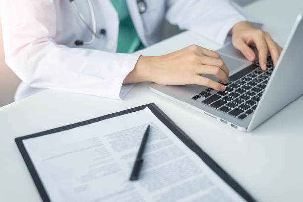 Concentrated Asian woman Doctor hands using laptop computer and working on checklist paper symptoms of patients on a clipboard in the medical room of the hospital. stock photo