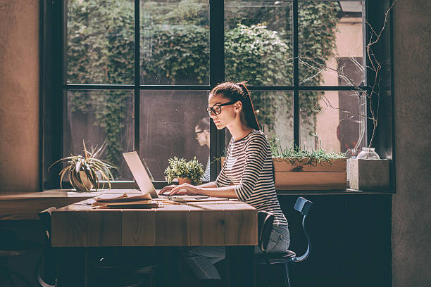 Concentrated at work. Confident young woman in smart casual wear working on laptop while sitting near window in creative office or cafe absorption stock pictures, royalty-free photos & images