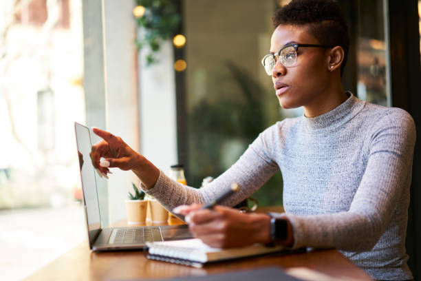 Concentrated attractive afro american female freelancer in casual outfit working with website designing writing down creative ideas into notebook to make concept planning sitting in coffee shop stock photo