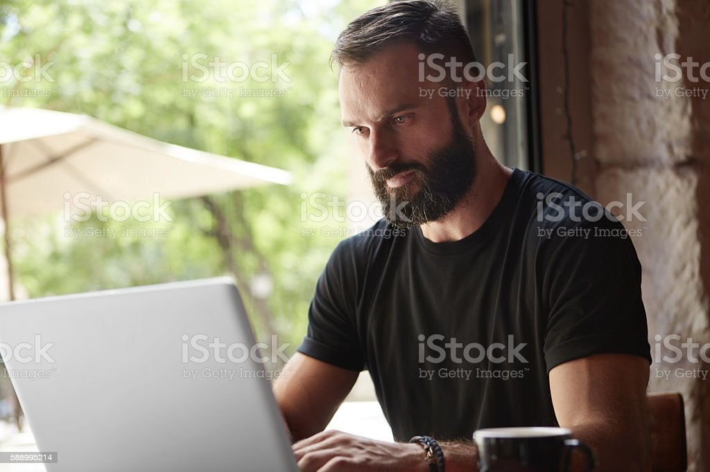 Concentrated Bearded Man Wearing Black Tshirt Working Laptop Wood Table стоковое фото