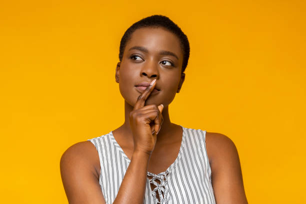 Concentrated black woman touching her lips and looking aside stock photo