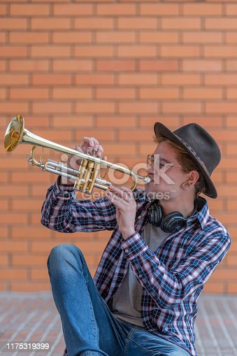 Concentrated blond boy with hat and glasses sitting on the floor playing a yellow trumpet, with a brick wall in the background out of focus. Concept of cultural youth. Vertical image
