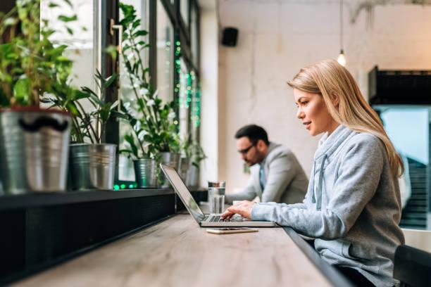 concentra el redactor mujer rubia trabajando en la tarea creativa en el café. - trabajo freelance fotografías e imágenes de stock