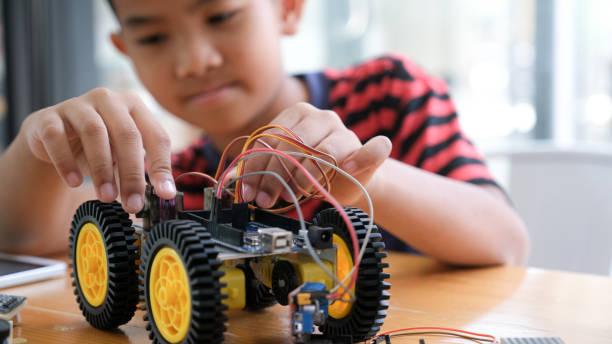 konzentrierter junge, der roboter im labor erstellt. - lernfortschrittskontrolle stock-fotos und bilder
