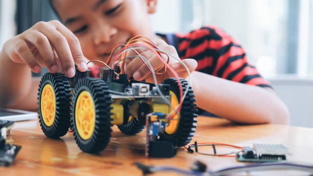 concentrated boy creating robot at lab. - plant stem stock pictures, royalty-free photos & images