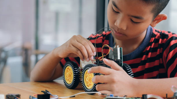 Concentrated boy creating robot at lab. stock photo