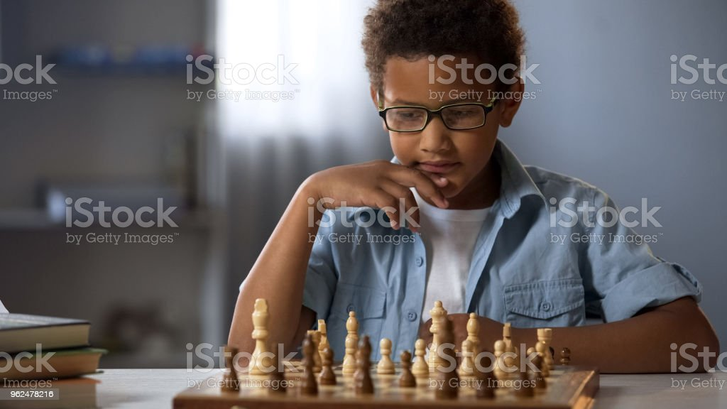 Concentrated boy developing chess strategy, playing board game with...
