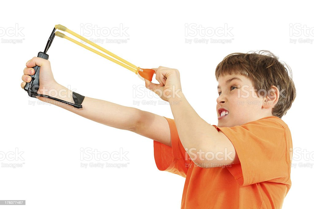 Concentrated boy with slingshot aim stock photo