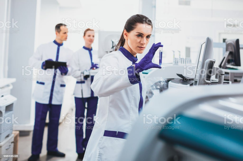 2d5fff83f3 Concentrated brunette female examining biological material - Stock image .