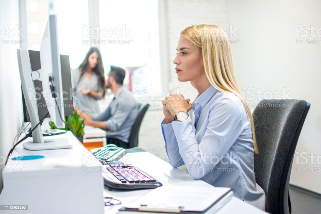 Concentrated business woman in front of computer in office Concentrated business woman in front of computer in office Adult Stock Photo