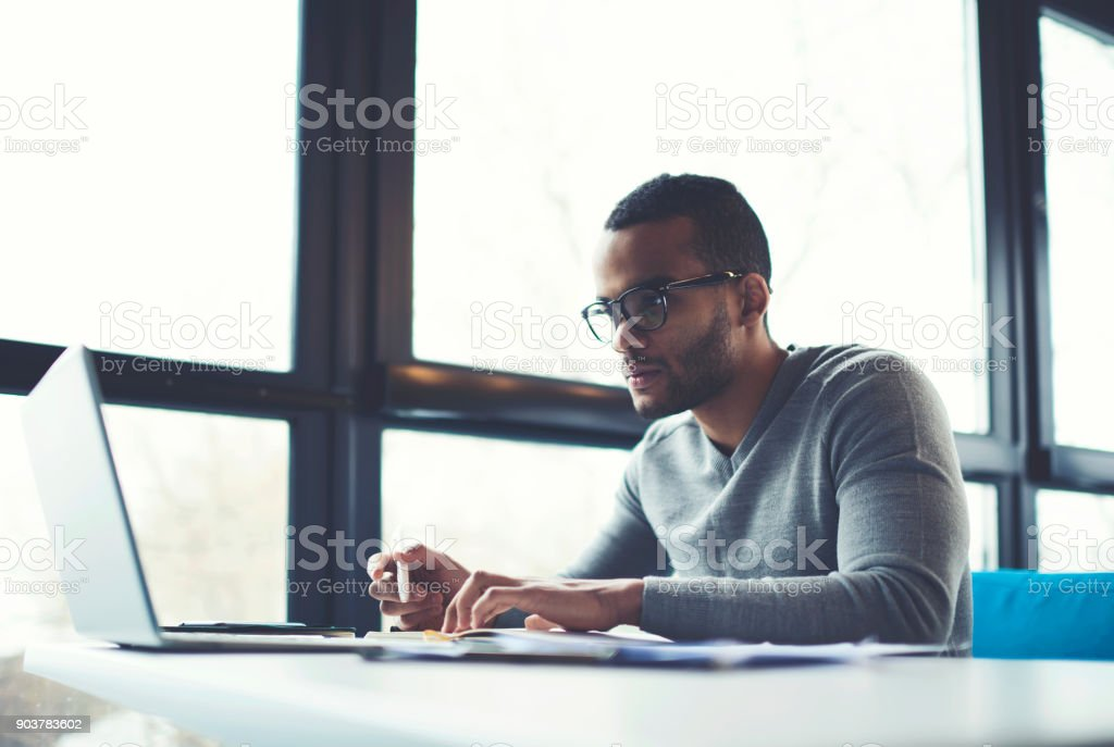 Concentrated businessman checking accounting documentation in online database on modern computer connecting to wireless internet connection. Male aro american entrepreneur working on laptop indoors stock photo