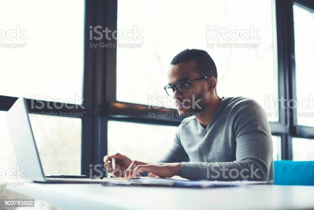 Concentrated Businessman Checking Accounting Documentation In Online Database On Modern Computer Connecting To Wireless Internet Connection Male Aro American Entrepreneur Working On Laptop Indoors Stock Photo - Download Image Now