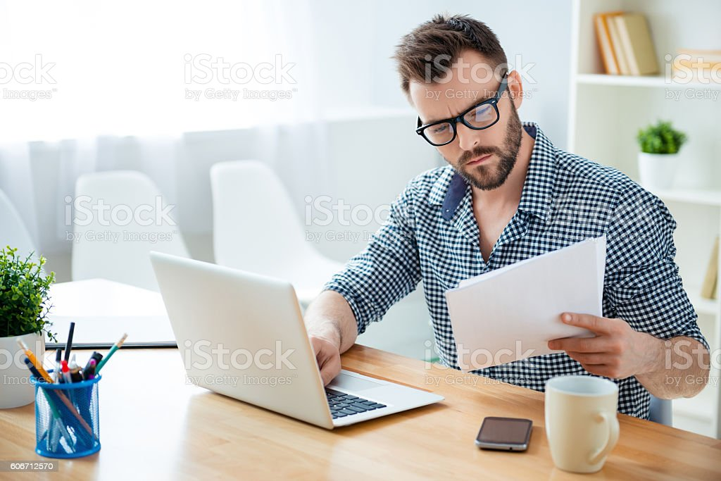 concentrated businessman in glasses with laptop reading contract - foto de acervo