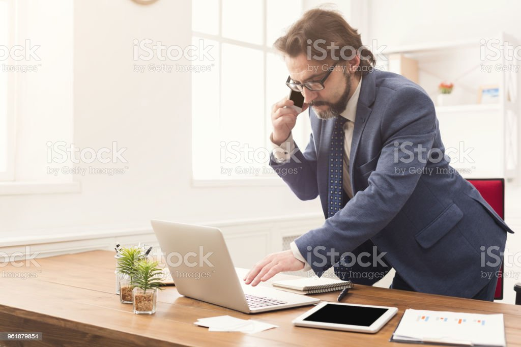 Concentrated businessman talking on mobile phone royalty-free stock photo