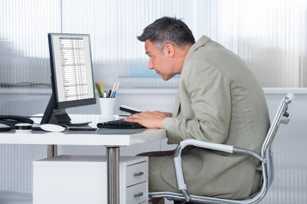 Concentrated Businessman Using Computer At Desk Side view of concentrated businessman using computer at desk in office bad posture stock pictures, royalty-free photos & images