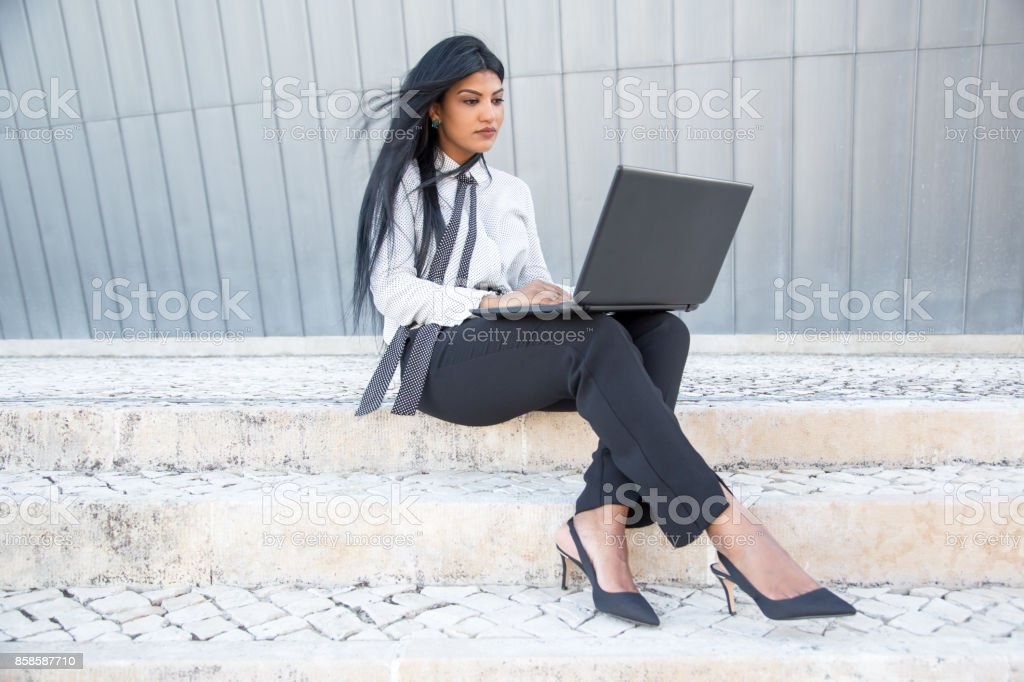 Concentrated businesswoman typing on laptop stock photo