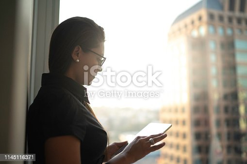 istock Concentrated businesswoman using tablet in front of window 1145116371