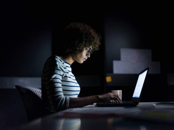 Concentrated businesswoman working late hours with her laptop stock photo