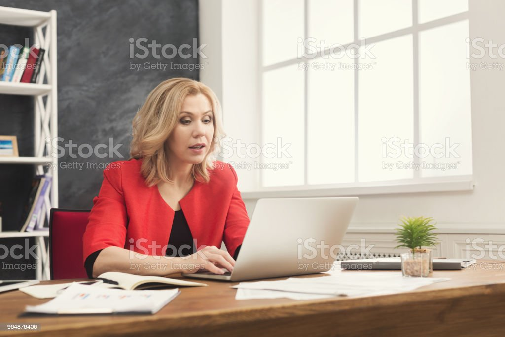 Concentrated businesswoman working on laptop at office royalty-free stock photo