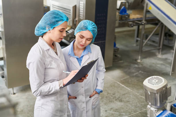 Concentrated busy food manufacturing workers in caps and lab coats analyzing data in clipboard and filling paper after production expertise stock photo