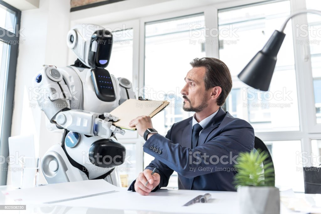 Concentrated confident mature man working with android stock photo