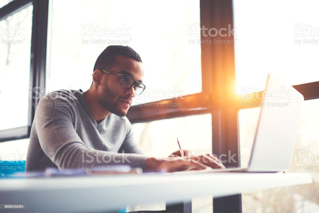 Concentrated dark skinned copywriter in eyewear typing text of publication for web site working on freelance, serious afro american student searching information for homework project in network stock photo